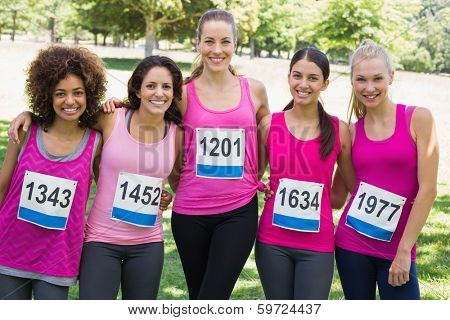Portrait of confident women participating in breast cancer marathon in park