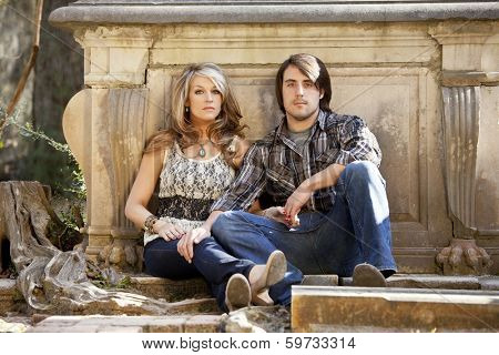 young sexy couple seated in cemetery, edgy portrait