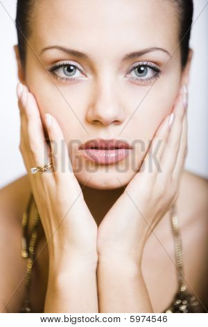 thoughtful young woman touching her face by hands