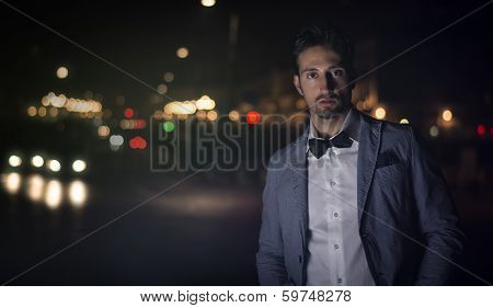 Attractive Young Man At Night With City Lights Behind Him