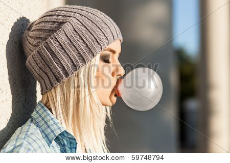Beautiful Blonde Girl In Hat with bubble gum