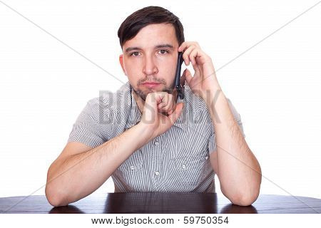 casual young man thinking and looking with a hand on his chin while speaking on the phone