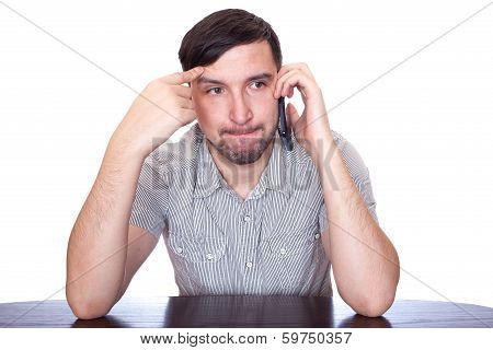 casual young man thinking and looking away with a hand on his head while speaking on the phone