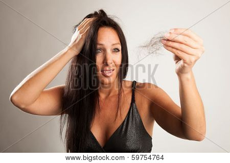 Beautiful woman is looking shocked to her hair