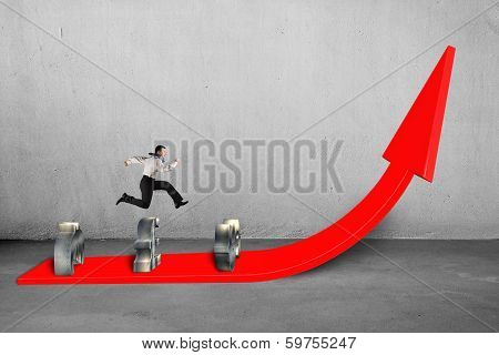 Businessman Jumping Over Money Symbols On Growing Red Arrow