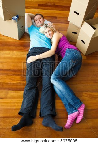 Happy Couple Relaxing On The Floor. Moving House