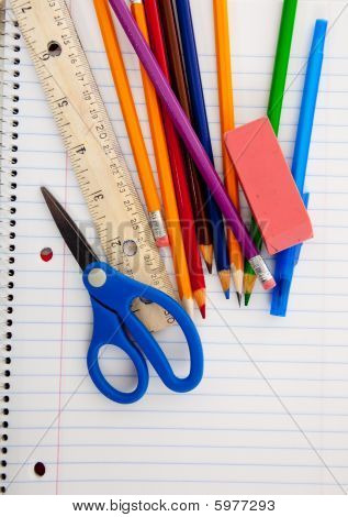 Assorted School Supplies On A Lined Notebook