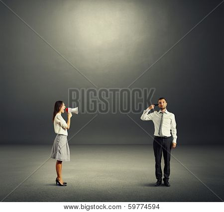 angry woman screaming at tired man with gun in the dark room