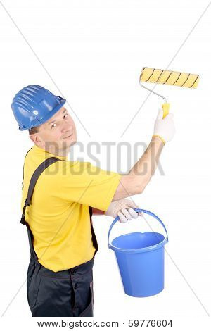 Worker in hardhat paints.