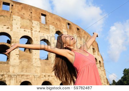 Happy carefree elated travel woman by Colosseum, Rome, Italy with arms raised out and up in ecstatic happiness expression. Travel concept with beautiful mixed race Asian woman in front of Coliseum.