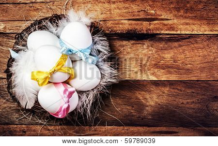 Easter Nest With Eggs,  Ribbons And White Feathers On Wooden Background With Copy Space For Text In