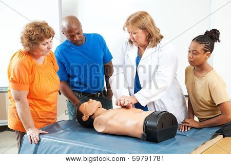 Adult education students learning CPR and first aid from a doctor or nurse.