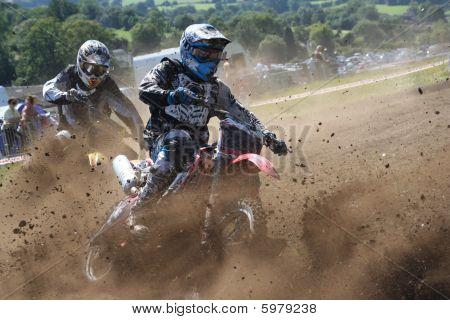 Dirt Bikes battle the corner in a cloud of mud : Bigstock