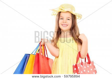 Cute girl in fancy clothes holding shopping bags isolated on white background