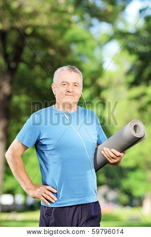 Smiling mature man holding an exercising mat and posing in a park