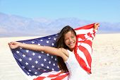 stock photo of patriot  - Beautiful patriotic vivacious young woman with the American flag held in her outstretched hands standing in the summer sunshine in front of an expanse of white sand and distant mountains - JPG
