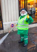 PARIS, FRANCE - JANUARY 4, 2012: Elderly worker washes street with mini wash. Paris is one of the ve