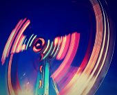 image of carnival ride  - a fair ride shot with a long exposure at night done with a retro vintage instagram filter - JPG