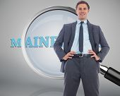 Cheerful businessman with hands on hips against magnifying glass showing mainframe word