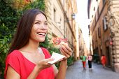 Pizza woman eating pizza slice in Rome, Italy smiling happy outdoors during travel vacation holiday.
