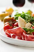 stock photo of antipasto  - Italian antipasto with ham green and red tomato olive basil rosemary and red wine selective focus - JPG