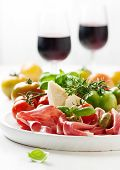 pic of antipasto  - Italian antipasto with ham green and red tomato olive basil rosemary and red wine selective focus