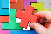 stock photo of orifice  - putting cross shaped piece in wooden multicoloured puzzle isolated on white background - JPG