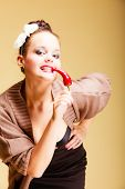 foto of flirtatious  - Portrait beautiful seductive woman fashion girl retro style holding biting spicy hot red cayenne chilli pepper - JPG