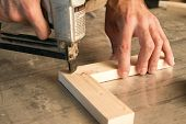 stock photo of joinery  - joinery uses a nail gun to attach pieces of wood - JPG