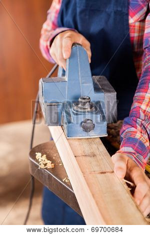 Midsection of female carpenter using electric planer on wood in workshop