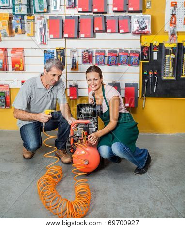 Full length portrait of saleswoman assisting male customer in using air compressor at hardware store