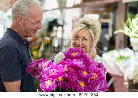 Happy Husband Smiling As He Gives His Wife Flowers