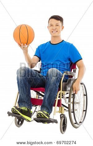 Hopeful Young Man Sitting On A Wheelchair With A Basketball