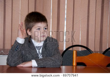First Grade Boy With His Hand Raised At The Desk