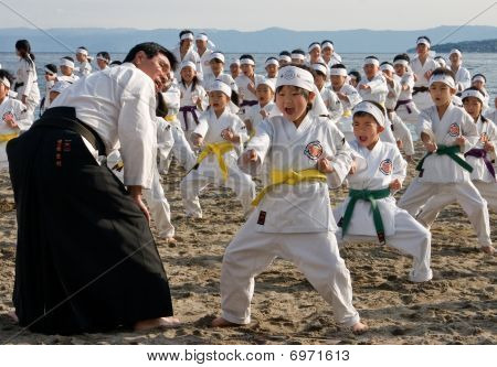 Young Karate students practice on a cold beach