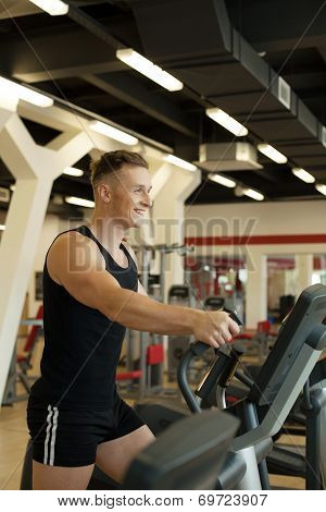 Merry young man exercising on treadmill