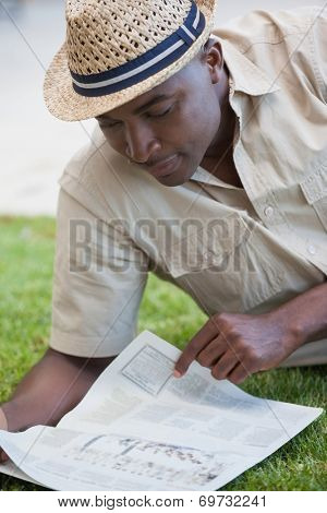 Man relaxing in his garden reading newspaper on a sunny day