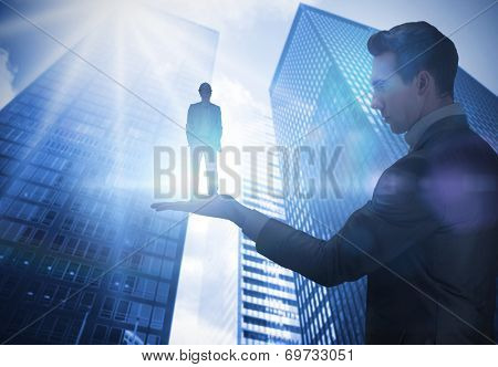 Composite image of businessman holding architect against low angle view of skyscrapers