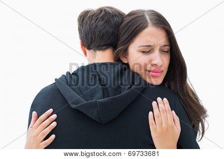 Unhappy brunette hugging her boyfriend on white background