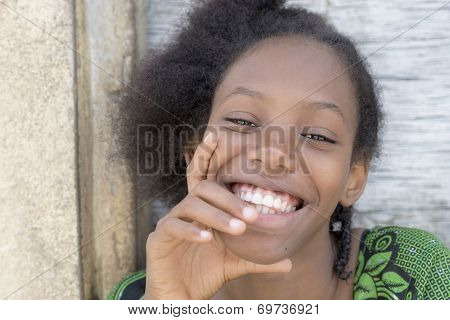 Natural Afro beauty seated in front of her house