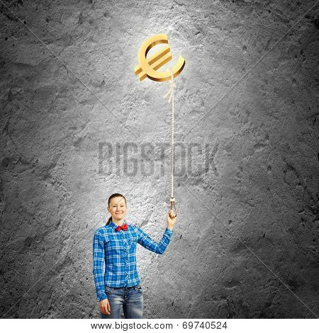 Young woman holding balloon shaped like euro sign