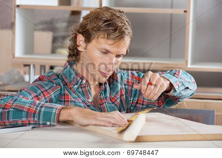 Mid adult male carpenter measuring wooden plank at table in workshop
