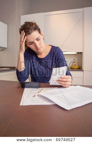 Unemployed and divorced woman with debts reviewing her monthly bills