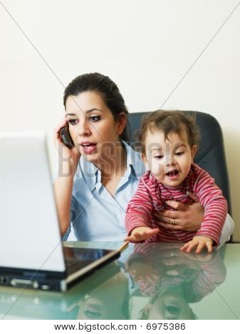 Businesswoman On The Phone, Holding Daughter