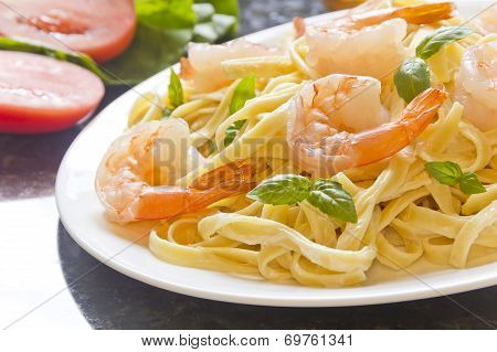 shrimp Fettuccini Alfredo with fresh basil leaves in fancy arrangement