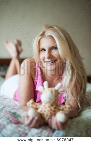 young beautiful woman relaxing with a toy on the bed