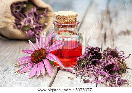 Essential Oil And Coneflowers On Wooden Rustic Table, Bag With Herbs