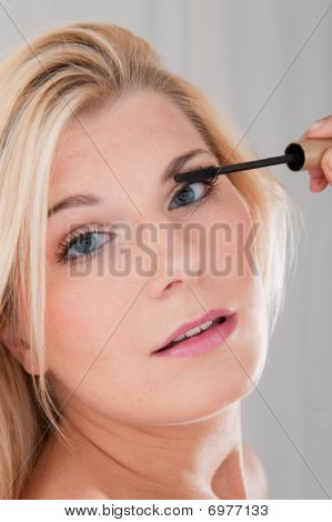 young beautiful woman applying mascara