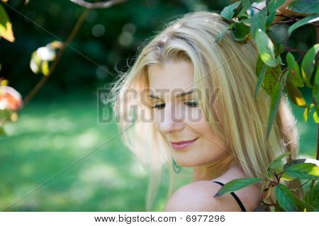 young spring woman in green forest standing near a tree