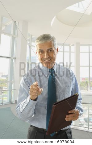 Middle Aged Businessman Holding Folder And Pointing